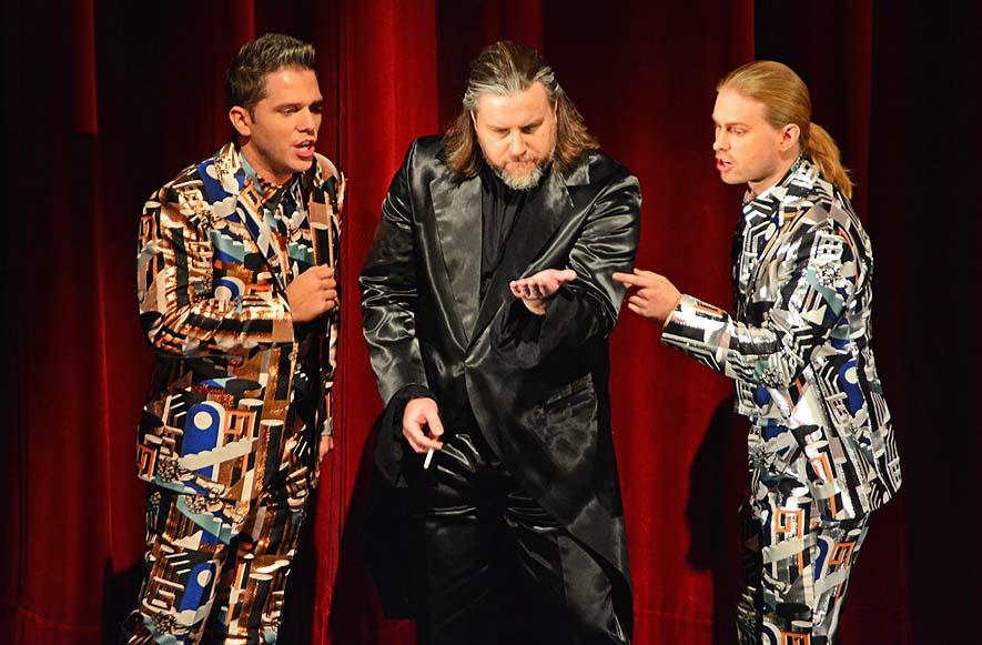 """1. Akt, """"Cosi Fan Tutte"""", Don Alfonso (Noel Bouley) wettet mit Ferrando (Paolo Fanale) und Guglielmo (John Ehest), dass Frauen nicht treu sein können, Deutsche Oper 2016 Foto: Holger Jacobs"""